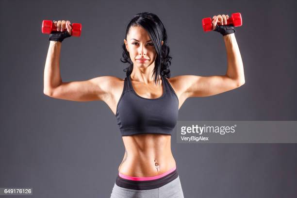 Fitness female with muscular body ready wearing hand gloves for workout on grey background