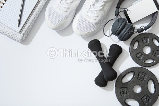 Fitness flat lay, dumbbells, notebook, headphones, notebook, towel on white background : Stock Photo