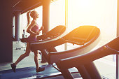 Fitness girl running on treadmill. Woman with muscular legs in gym