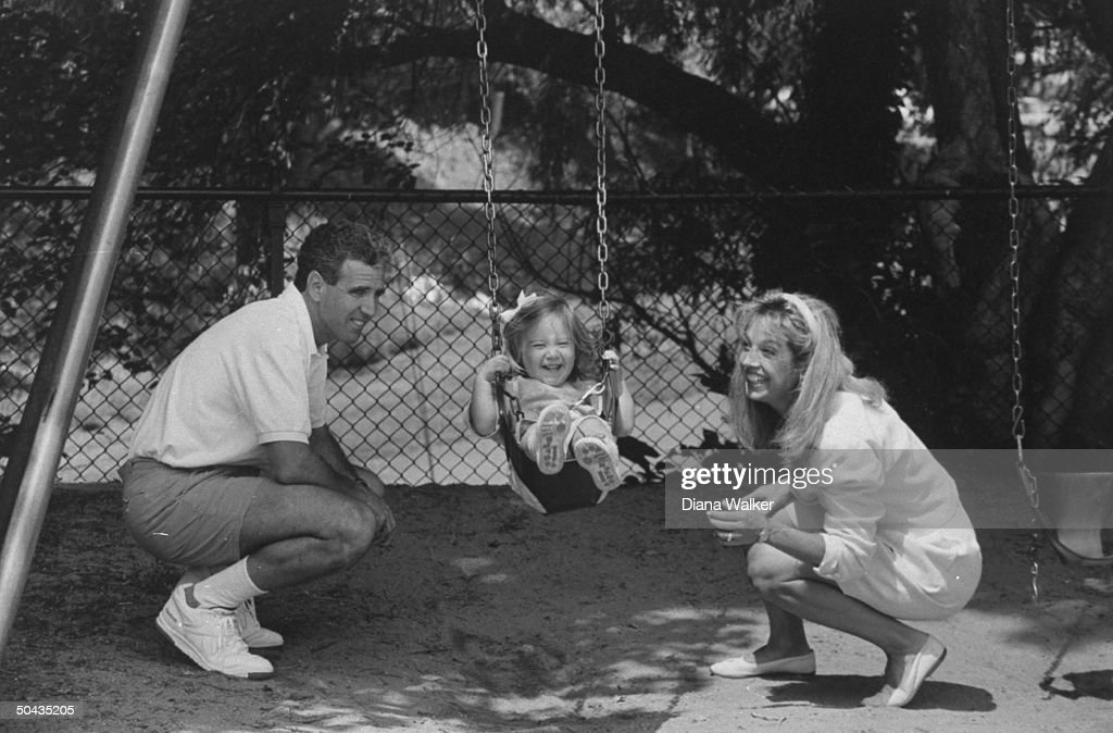 Fitness guru Denise Austin & husband Jeff watch their 21-mo-old daughter Kelly on a swing at a park nr. their home.
