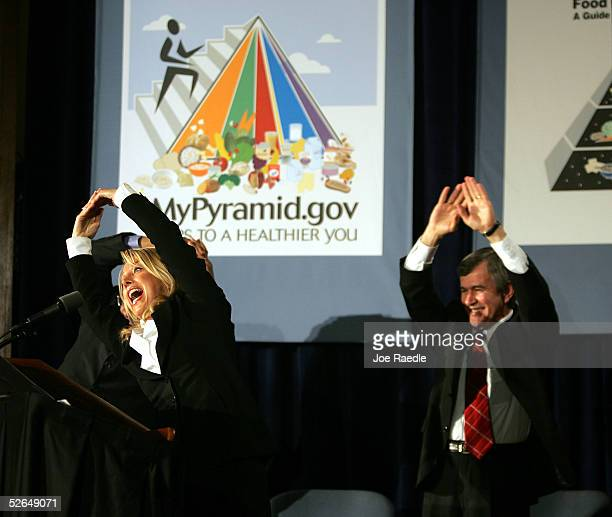 Fitness Guru Denise Austin performs a stretching exercise with Agriculture Secretary Mike Johanns during the unveiling of the MyPyramid a new symbol...