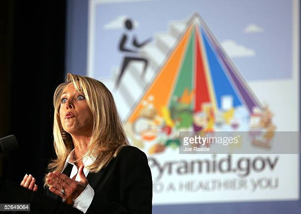 Fitness guru Denise Austin speaks in front of a poster that shows the MyPyramid a new symbol and interactive food guidance system replaces the old...