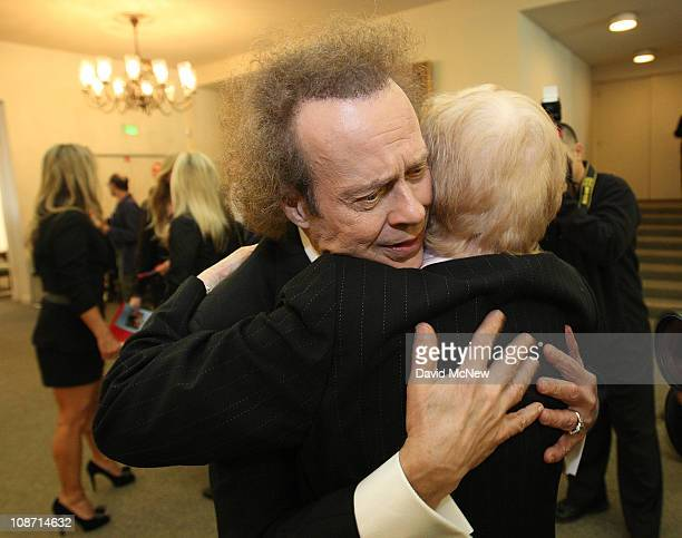 Fitness guru Richard Simmons hugs Elaine LaLanne widow of the first television fitness guru Jack LaLanne before the start of the funeral service for...