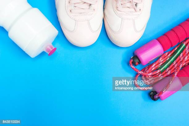 Fitness, healthy and active lifestyles Concept, male and female sport shoes and skipping rope on blue background,water,