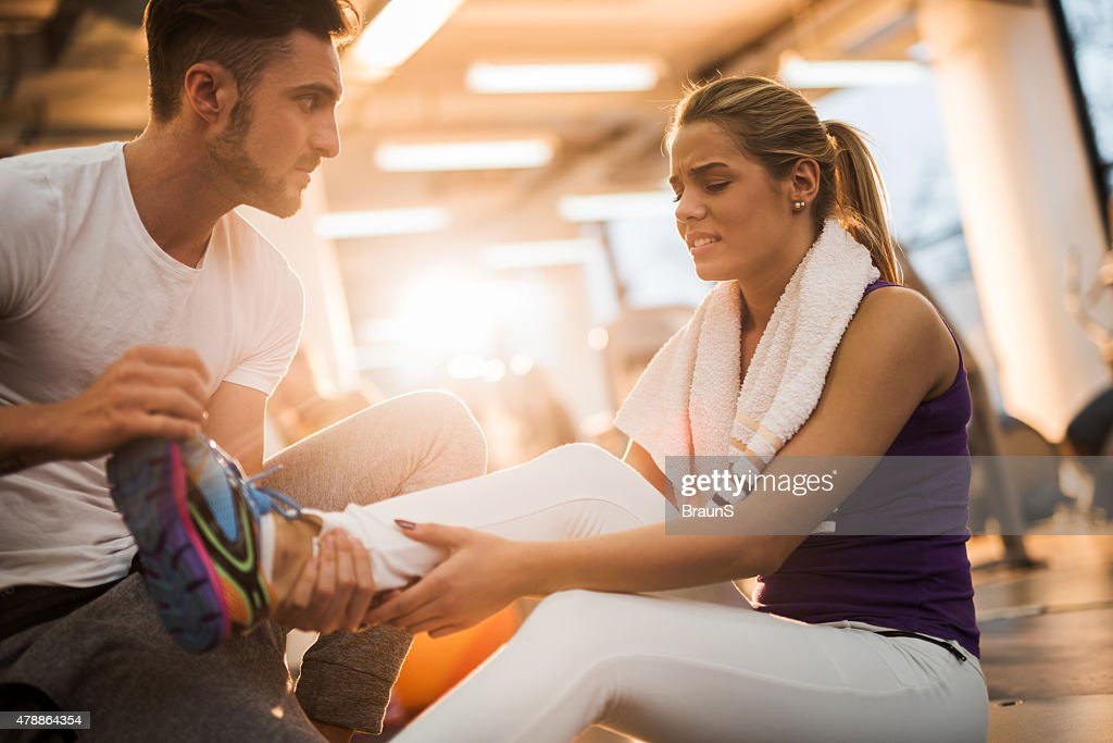 Fitness instructor assisting young woman who had injured herself. : Stock Photo