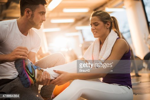 Fitness instructor assisting young woman who had injured herself.