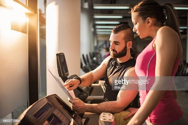 Instrutor de Fitness fazendo um plano com uma mulher na passadeira rolante.