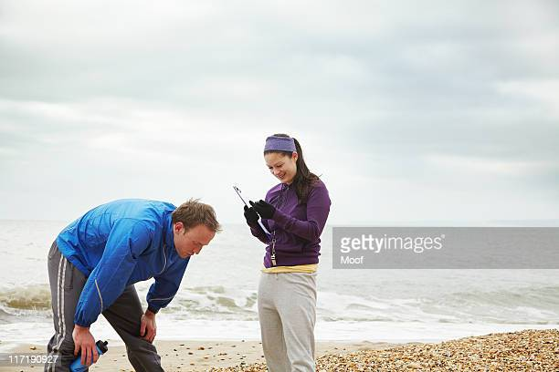 Fitness instructor with man on beach