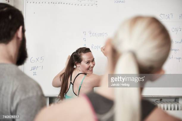 Fitness instructor writing on whiteboard in cross training gym