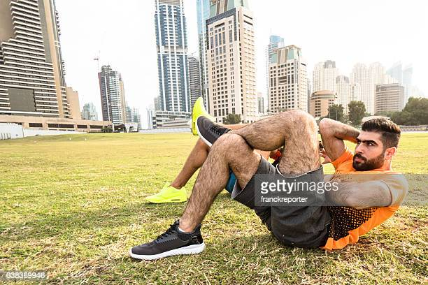 Fitness man doing cruch abs in Dubai marina