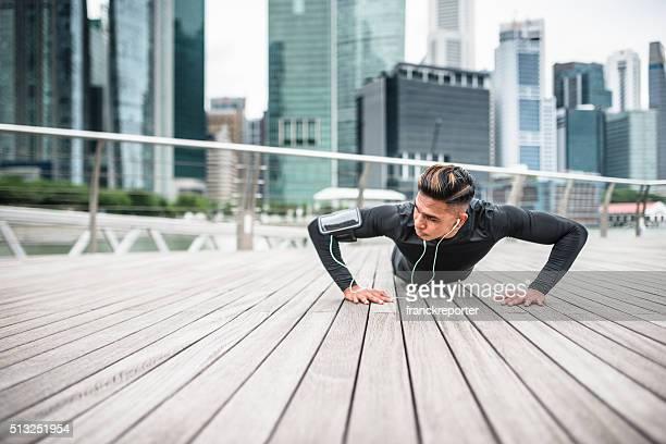 Fitness man doing push-ups in singapore city