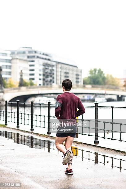 Fitness man running in Berlin under the rain