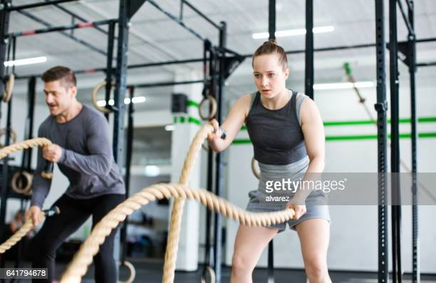 Fitness people exercising with battle ropes