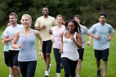 A diverse group of young adults exercising outside.