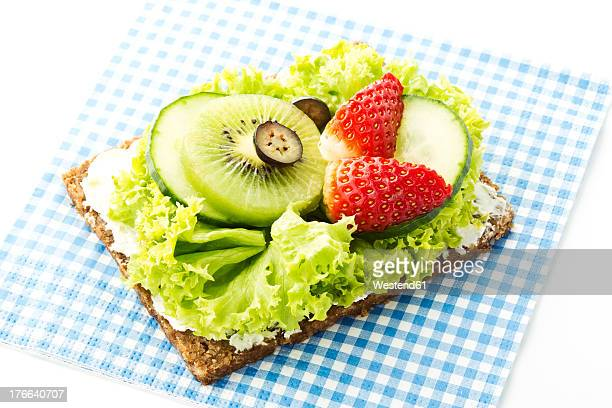 Fitness sandwich with cream cheese, lettuce and slices of fruits on white background, close up