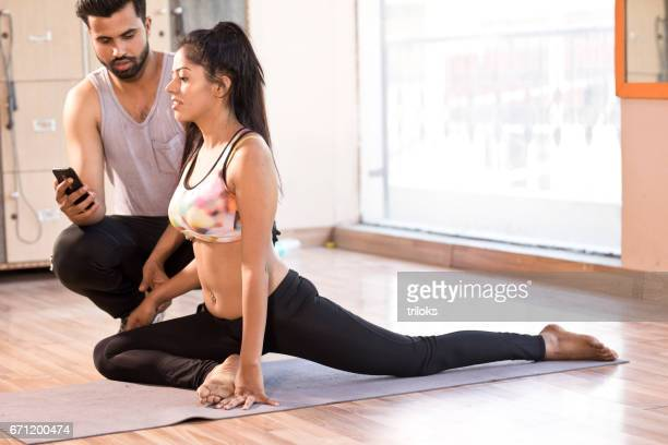 Fitness trainer helping woman in stretching