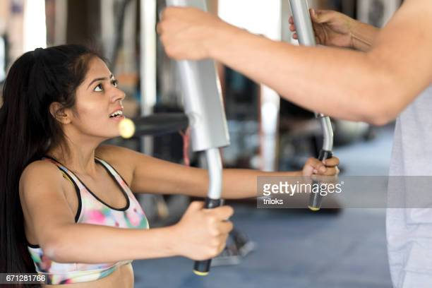 Fitness trainer helps woman exercising at the gym