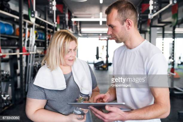 Fitness trainer in gym talking to new client, giving her advices for future achievements.