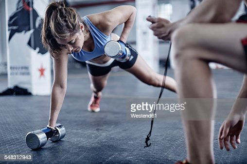 Fitness trainer keeping time with woman doing dumbell push-ups