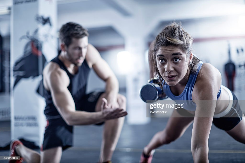Fitness trainer watching woman doing dumbell push-ups