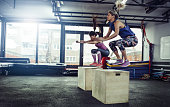 Female athletes doing box jump workout at gym.