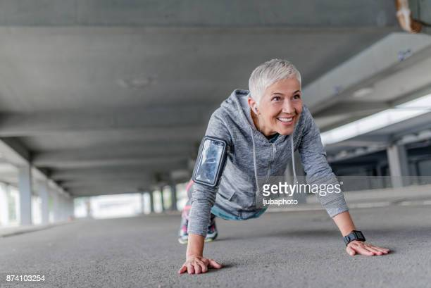 Fitness woman doing push-ups during outdoor cross training workout