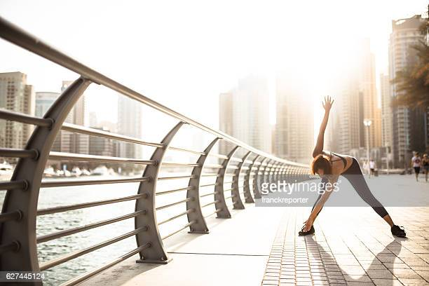 fitness woman doing stretching in dubai marina
