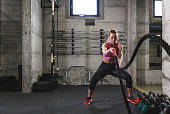 Fitness woman exercise in the gym with battle rope.