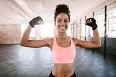 Portrait of young fitness woman flexing muscles and smiling. African female model in sportswear showing her muscles.
