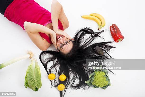 Fitness woman laying with vegetables