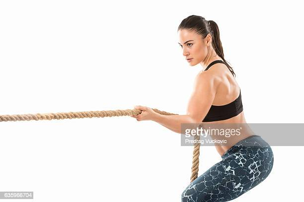 Fitness woman pulling ropes