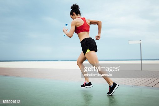 Fitness woman running at the beach coast : Photo