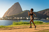 Young Fitness Woman Running on a Dirt Road in the Morning, Sugarloaf Mountain in the Horizon.