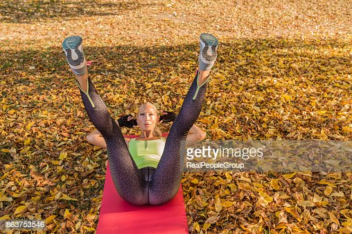 Fitness woman training outside in autumn park. Sport woman doing exercises during workout : Stock Photo