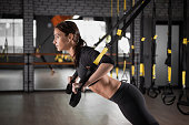 Beautiful fitness woman training with  fitness straps. Suspension exercising in gym