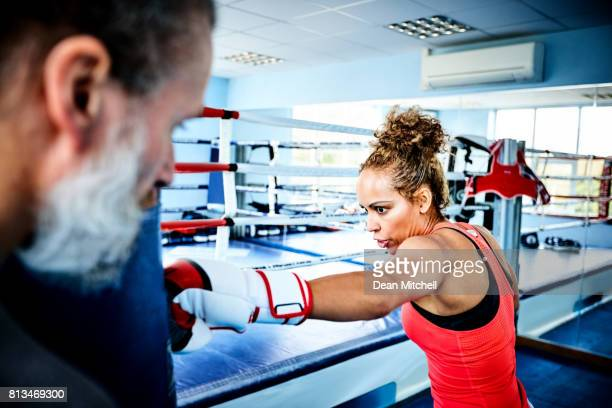Fitness woman training with punching bag in gym