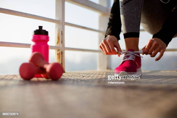 Fitness woman tying shoes close up