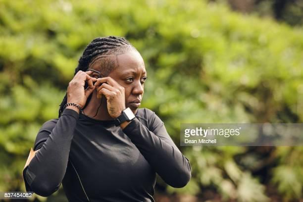 Fitness women adjusting earphone in the park