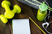 Blank copy space workout routine notebook, detox green smoothie, dumbbells and earphones on wooden table for dieting and healthy fitness nutrition concept.  Diet and training planning.