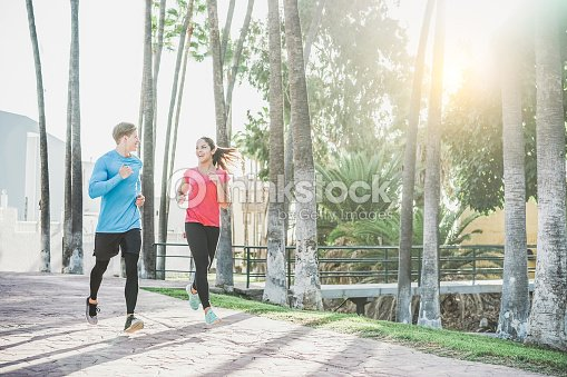 Fitness Young Couple Running Outdoor With Palms In