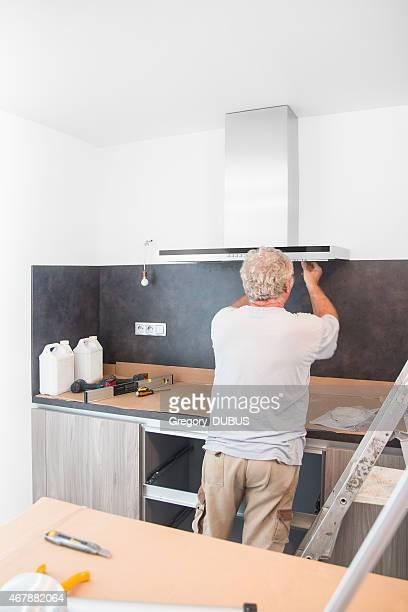 Fitter men installing range hood in new kitchen