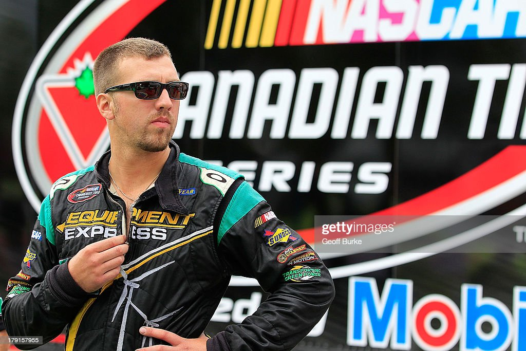 J.R. Fitzpatrick, driver of the #84 Equipment Express Chevrolet, stands next to his car during qualifying for the NASCAR Canadian Tire Series presented by Mobil 1 Pinty's presents the Clarington 200 at Canadian Tire Motorsport Park on August 31, 2013 in Bowmanville, Canada.