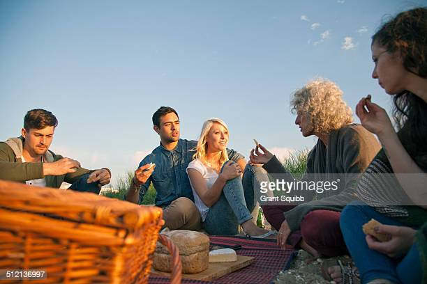 Five adult friends having picnic on Bournemouth beach, Dorset, UK