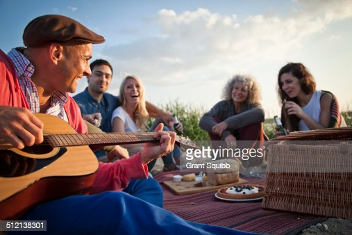 Five adult friends picnicing on Bournemouth beach, Dorset, UK