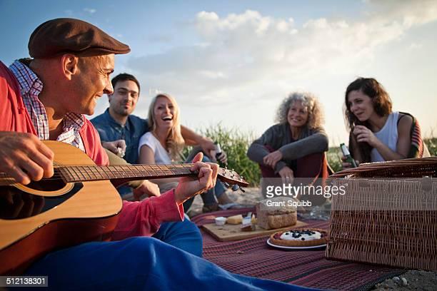 Five adult friends picnicing on Bournemouth beach, Dorset, UK