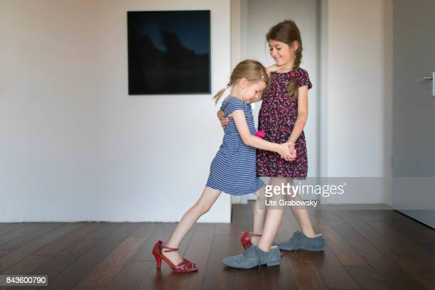 A five and a sevenyearold girl play up and dance tango in too big shoes on August 07 2017 in Bonn Germany