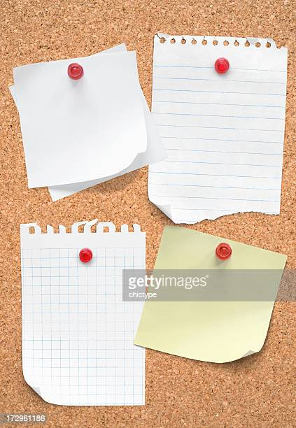 Five blank pieces of paper tacked to cork board