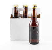 Five beer bottles in cardboard container with gold caps with side of carrier facing camera and single bottle standing on table top
