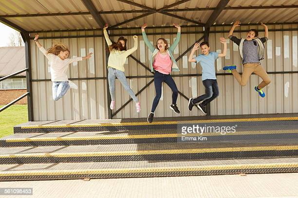Five boys and girls jumping mid air in stadium stand