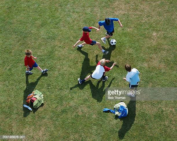 Five boys (10-12) playing football, overhead view
